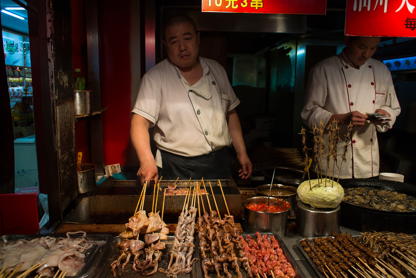 Beijing, China - October 13, 2013: Cooks grilling local fast food delicacies of scorpions, locusts, starfish, squid and other in the busy night markets of Wangfujing in the heart of Beijing, China's vibrant capital city.