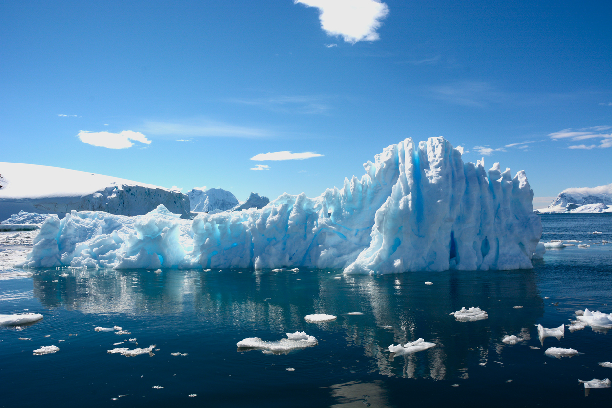 Stunning shot of an iceberg against dark blue waters and sky